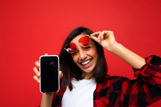 Foto einer schönen lächelnden jungen frau, die gut aussieht und ein lässiges, stilvolles rotes hemd mit weißem t-shirt trägt