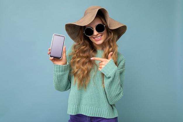 Foto einer schönen lächelnden jungen frau, die gut aussieht und ein lässiges, stylisches outfit trägt, das isoliert auf dem hintergrund steht, mit kopienraum, der das smartphone hält und das telefon in der hand mit leerer bildschirmanzeige für zeigt