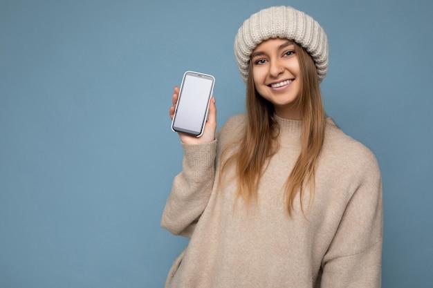 Foto einer schönen lächelnden, positiv aussehenden jungen frau, die einen stylischen beige pullover und beige trägt