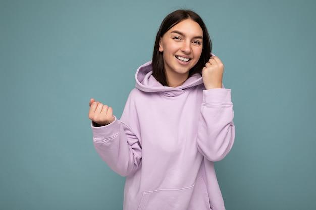 Foto einer schönen, positiv lächelnden erwachsenen frau, die stilvolle kleidung trägt, die einzeln auf buntem hintergrund mit kopienraum steht und in die kamera schaut