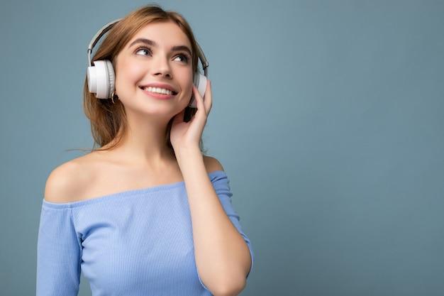 Foto einer schönen positiv lächelnden jungen blonden frau mit blauem bauchfreiem oberteil isoliert über blau