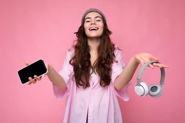 Foto einer schönen, positiv lächelnden jungen frau, die ein stilvolles, lässiges outfit trägt, isoliert auf bunt