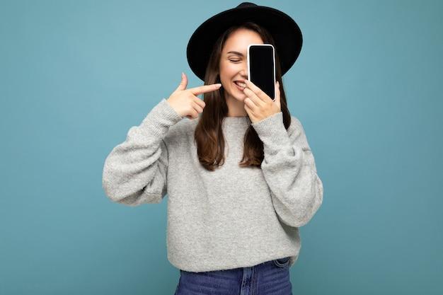 Foto einer schönen positiven frau mit schwarzem hut und grauem pullover mit mobiltelefon