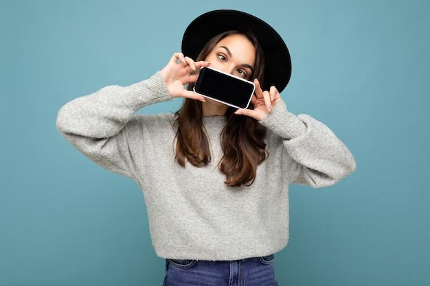 Foto einer schönen positiven jungen weiblichen person mit schwarzem hut und grauem pullover, die ein mobiltelefon hält und das smartphone einzeln auf dem hintergrund mit blick auf die kamera zeigt