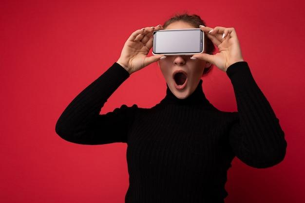 Foto einer schönen schockierten jungen brünetten frau, die einen schwarzen pullover trägt, der isoliert auf rotem hintergrund steht und ein mobiltelefon mit leerem bildschirm für ein modell mit offenem mund zeigt.