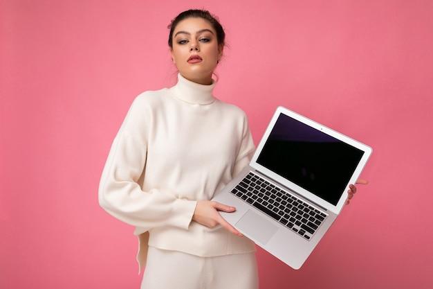 Foto einer schönen, selbstbewussten, arroganten jungen frau mit dunklen haaren, die einen weißen pullover trägt, der einen computer-laptop hält und die kamera einzeln auf rosafarbenem wandhintergrund betrachtet.