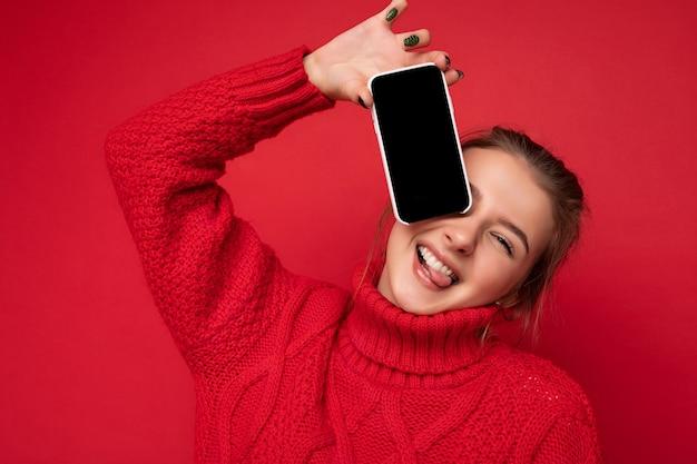 Foto einer schönen, süßen, lächelnden jungen frau, die einen warmen roten pullover trägt, isoliert über einer roten hintergrundwand, die smartphone hält und ein telefon mit leerem display für das modell mit blick auf die kamera zeigt.