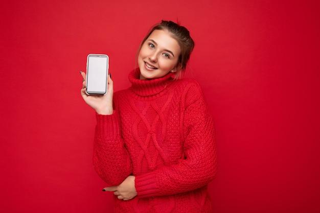Foto einer schönen, süßen, lächelnden jungen frau, die einen warmen roten pullover trägt, isoliert über einer roten hintergrundwand, die smartphone hält und ein telefon mit leerem display für ein modell mit blick in die kamera zeigt?