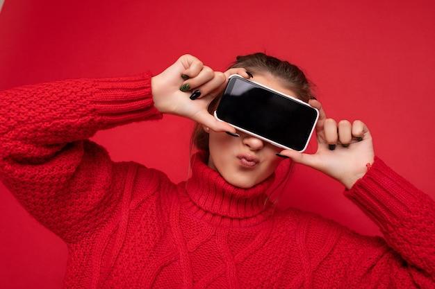 Foto einer schönen, süßen, lächelnden jungen frau, die einen warmen roten pullover trägt, isoliert über einer roten hintergrundwand, die smartphone hält und ein telefon mit leerem display für mockup zeigt.