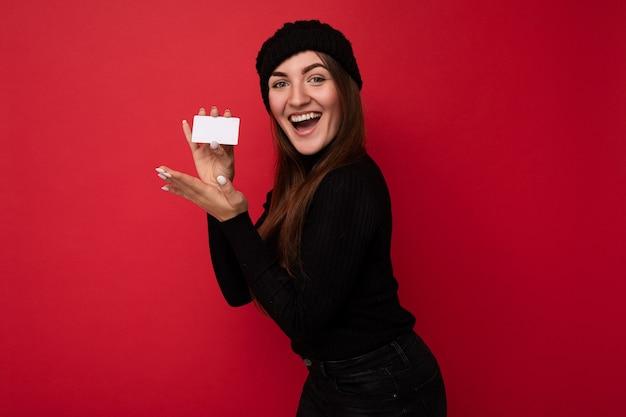 Foto einer schönen überraschten jungen brünetten frau mit schwarzem pullover und hut isoliert auf rotem hintergrund mit kreditkarte, die in die kamera schaut.