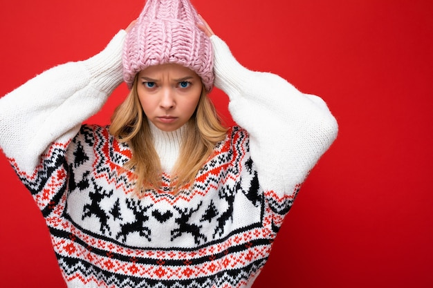 Foto einer schönen unzufriedenen traurigen jungen blonden frau, die über einer roten hintergrundwand isoliert ist und einen winterpullover und einen rosa hut mit blick auf die kamera trägt