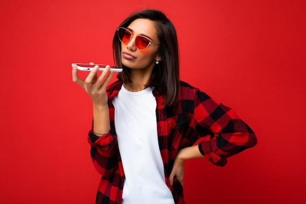 Foto einer schönen verärgerten jungen brunet-frau, die ein stilvolles rotes hemd, weißes t-shirt und eine rote sonnenbrille trägt, die auf rotem hintergrund isoliert ist und die sprachnachricht mit dem handy aufzeichnet, die zur seite schaut.