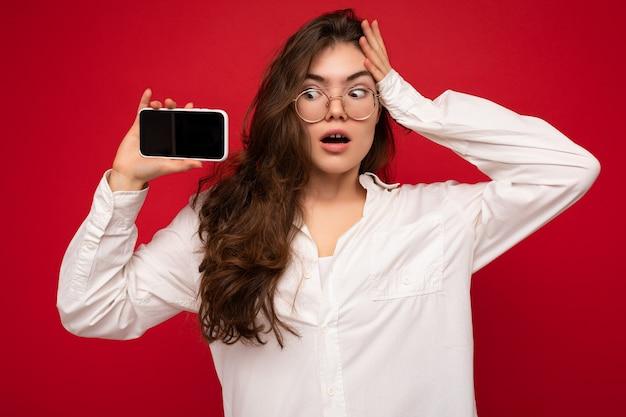 Foto einer sexy erstaunten schönen jungen brünetten frau, die ein weißes hemd und eine optische brille trägt, isoliert