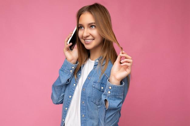 Foto einer sexy schönen glücklichen jungen blonden frau, die ein lässiges blaues jeanshemd trägt, isoliert über rosa