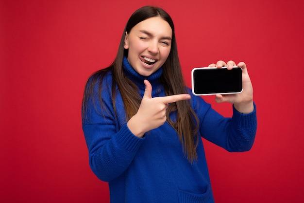 Foto einer sexy schönen lächelnden jungen frau, die gut aussieht und ein lässiges, stylisches outfit trägt, das isoliert auf dem hintergrund steht, mit kopienraum, der das smartphone hält, das telefon in der hand mit leerem bildschirm zeigt