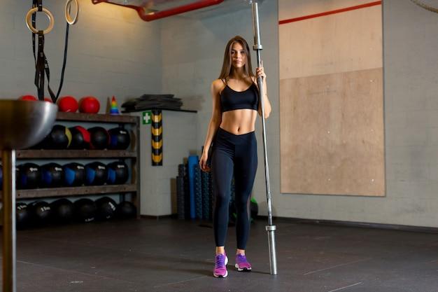Foto einer sportlich attraktiven frau in schwarzer enger kleidung, die im fitnessstudio steht und eine metallstange in der hand vor dem hintergrund von sportgeräten hält