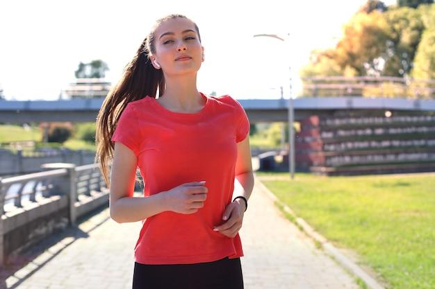 Foto einer sportlichen schlanken frau, die sportkleidung trägt und musik mit kopfhörern hört, während sie in der nähe der stadt am flussufer trainiert.