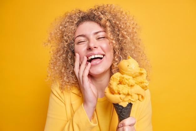 Foto einer überglücklichen, lockigen frau, die sich amüsiert lächelt, hält die augen geschlossen und genießt es, köstliches eis mit mangogeschmack zu essen, mit leckerem gefrorenem dessert einzeln auf gelber wand.