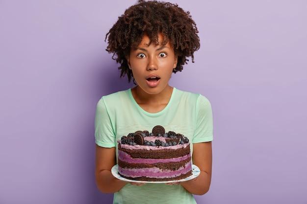 Foto einer überraschten dunkelhäutigen frau mit lockigem haarschnitt, hält köstlichen kuchen, überraschte gäste aßen bereits auf der schwelle, gekleidet in freizeitkleidung, gebackenes leckeres dessert