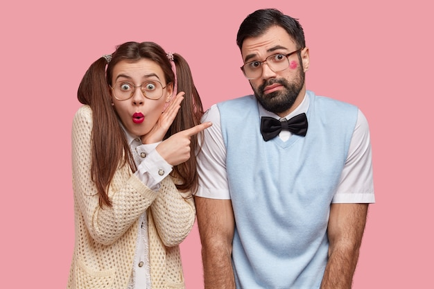 Foto einer überraschten europäischen frau mit zwei pferdeschwänzen, rotem lippenstift, zeigt auf zögernden freund, der kuss von ihr erhalten hat