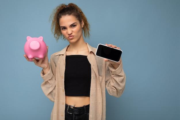 Foto einer unzufriedenen, zweifelhaften jungen, schönen, attraktiven, brünetten frau mit aufrichtigen emotionen, die ein stylisches beigefarbenes hemd einzeln auf blauem hintergrund mit kopierraum trägt, hält rosa schwein-penny-verbot