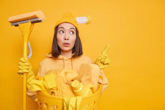Foto einer verwunderten asiatischen frau, die auf kopienraum zeigt, zeigt, dass etwas mit reinigungsmitteln posiert, während des geschäftigen samstags auf gelbem hintergrund wäsche gewaschen wird. hausarbeitskonzept