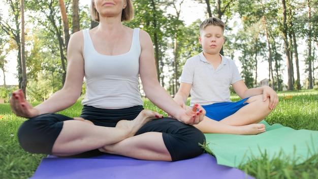 Foto einer yogalehrerin mittleren alters oder eines guru, der teenager beim yoga unterrichtet. frau mit junge meditiert und streckt sich auf gras im park