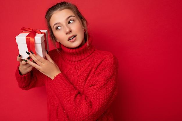 Foto einer ziemlich positiven, nachdenklichen, brünetten jungen frau, die über roter hintergrundwand isoliert ist und einen roten pullover trägt, der eine weiße geschenkbox mit rotem band hält und zur seite schaut. platz kopieren, mockup