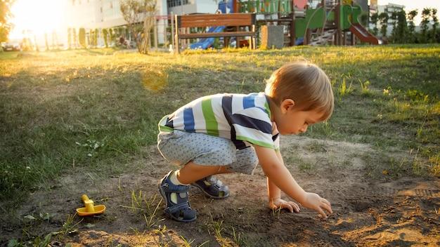 Foto eines 3-jährigen kleinen jungen, der im park auf dem boden sitzt und sand gräbt