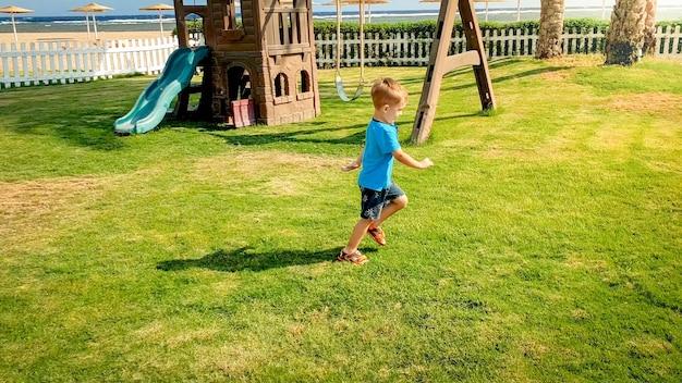 Foto eines 3 jahre alten kleinkindjungen, der auf einem großen spielplatz mit schönem grasrasen im park läuft