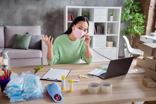 Foto eines asiatischen damengeschäfts, das medizinische maskenpakete für die gesichtsgrippe für die lieferung von boxen organisiert, die sprechende festnetzkunden chatten, schreiben die bestelldetails der zwischenablage im innenbereich im innenbereich