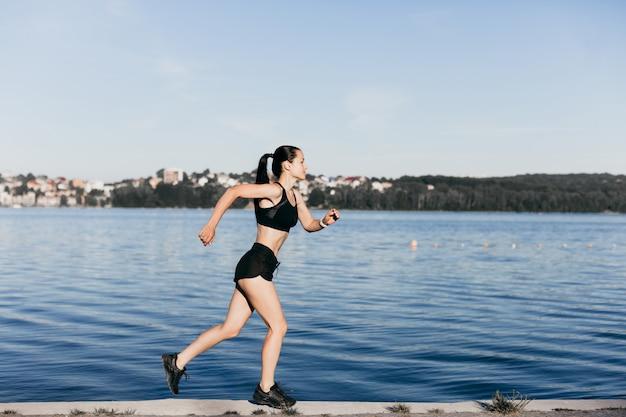 Foto eines athletischen mädchens, das in schwarz während eines morgenjoggens auf einem stadtstrand am morgen gekleidet ist.