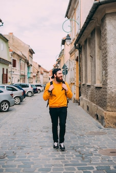 Foto eines bärtigen männlichen touristen, der auf alten europäischen straßen geht.