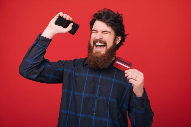 Foto eines bärtigen mannes, der sein erstes gehalt feiert, mit erhobenen händen und geschlossenen augen, rote wand