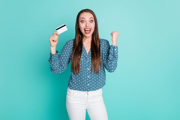 Foto eines ekstatischen mädchens, das kreditkarte hält, die faust tragen, weiße hose mit polka-dot-bluse, isoliert auf türkisfarbenem hintergrund