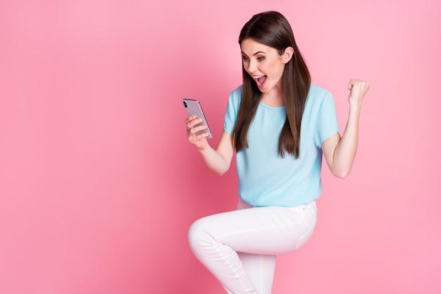 Foto eines ekstatischen mädchens, das smartphone benutzt, um die faust zu schreien, blaue weiße hose zu tragen, isoliert in pastellfarben
