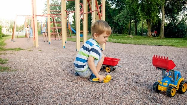 Foto eines entzückenden 3-jährigen kleinkindjungen, der mit sand spielt und du lkw und anhänger im park