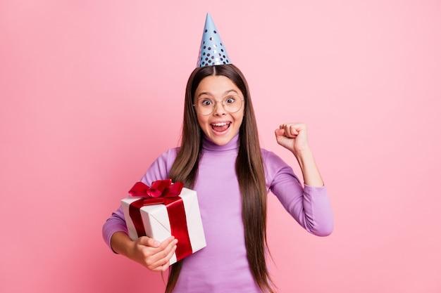 Foto eines entzückten kleinen mädchens, das eine geschenkbox hält, die fäuste hebt, trägt einen violetten geburtstagskegel, der auf pastellfarbenem hintergrund isoliert ist