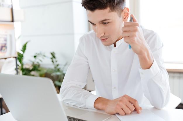Foto eines ernsten mannes in weißem hemd mit laptop-computer, während er den stift in den händen hält. coworking. computer betrachten.