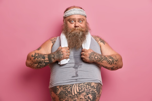 Foto eines ernsthaften kräftigen mannes in sportkleidung träumt von muskulösem körper, arbeitet hart an seinem körper, will abnehmen, hat tätowierte arme, dicken bauch, macht körperliche übungen mit fitnesstrainer