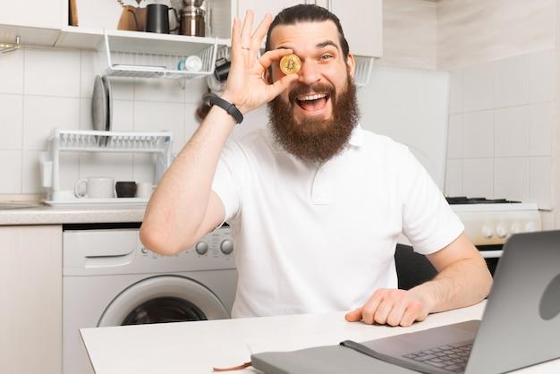 Foto eines erstaunten bärtigen mannes, der am laptop in der küche sitzt und bitcoin zeigt