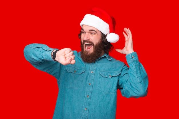 Foto eines erstaunten bärtigen mannes mit weihnachtsmann-hut, der auf die uhr schaut