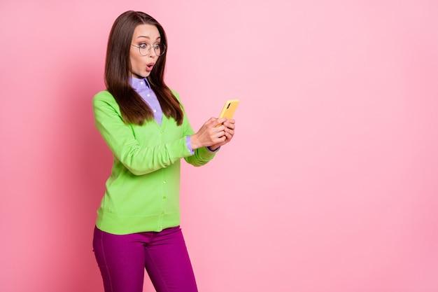 Foto eines erstaunten mädchens, das smartphone benutzt, trägt lila, gut aussehende kleidung, die über rosafarbenem hintergrund isoliert ist