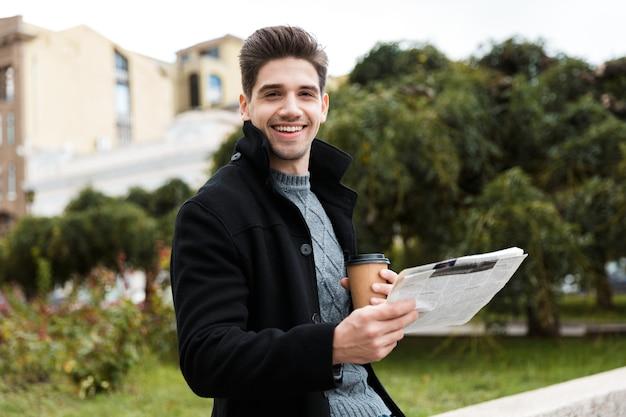 Foto eines fröhlichen mannes der 30er jahre, der eine jacke trägt, die zeitung liest und kaffee zum mitnehmen trinkt, während er durch den stadtpark geht?
