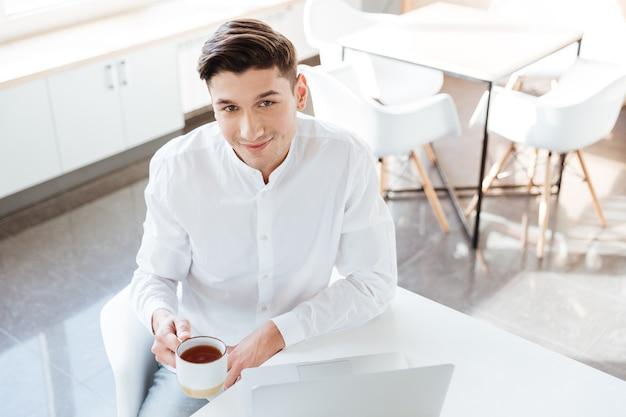Foto eines fröhlichen mannes im weißen hemd mit laptop-computer beim kaffeetrinken. coworking. blick in die kamera.