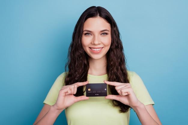 Foto eines fröhlichen promoter-mädchens, das eine debitkarte hält, die einen neuen bankservice auf blauem hintergrund präsentiert