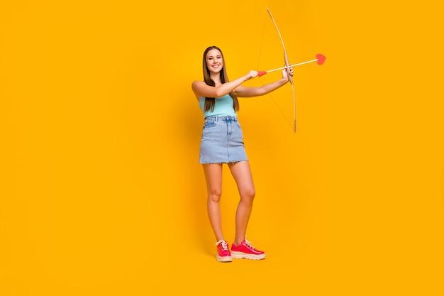 Foto eines fröhlichen teenagers, der einen stapel pfeile in den händen hält, isoliert auf gelbem hintergrund