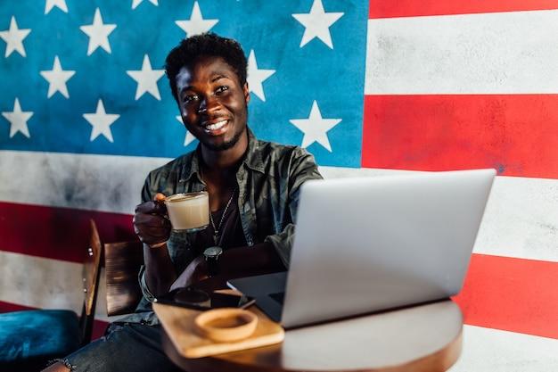 Foto eines glücklichen afrikanischen mannes, der in einem café sitzt und am laptop arbeitet, eine kaffeepause einlegen.