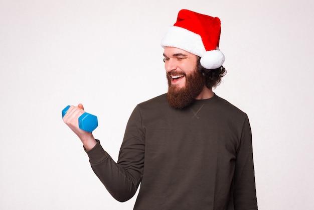 Foto eines glücklichen bärtigen mannes, der einen weihnachtsmann-hut trägt und mit einer kleinen blauen hantel arbeitet