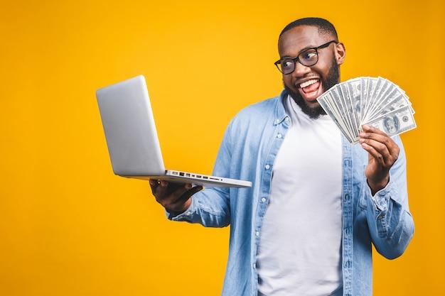 Foto eines glücklichen jungen afroamerikanischen gutaussehenden mannes, der unter verwendung des laptop-computers posiert, der geld hält.
